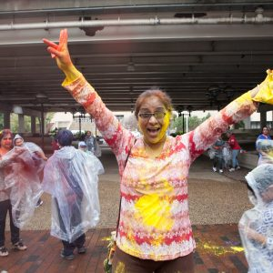 Young girl covered in yellow powder from Holi Festival.