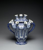 A tall, two-handled, urn-shaped tulip, or flower, vase of tin-glazed earthenware, with eight spouts on the body and seven on the conforming cover, the body decorated in blue on white ground with panels of hanging vines below large shell motifs, with lattice work and floral motifs in between, the waisted lower body with panels of fish scale motifs and four-lobed flowers, the foot with leaf motifs, the shoulder with stylized gadrooning, the spouts on the body each with floral and leaf motifs, the cover likewise in blue and white with a pattern of geometric and floral motifs.