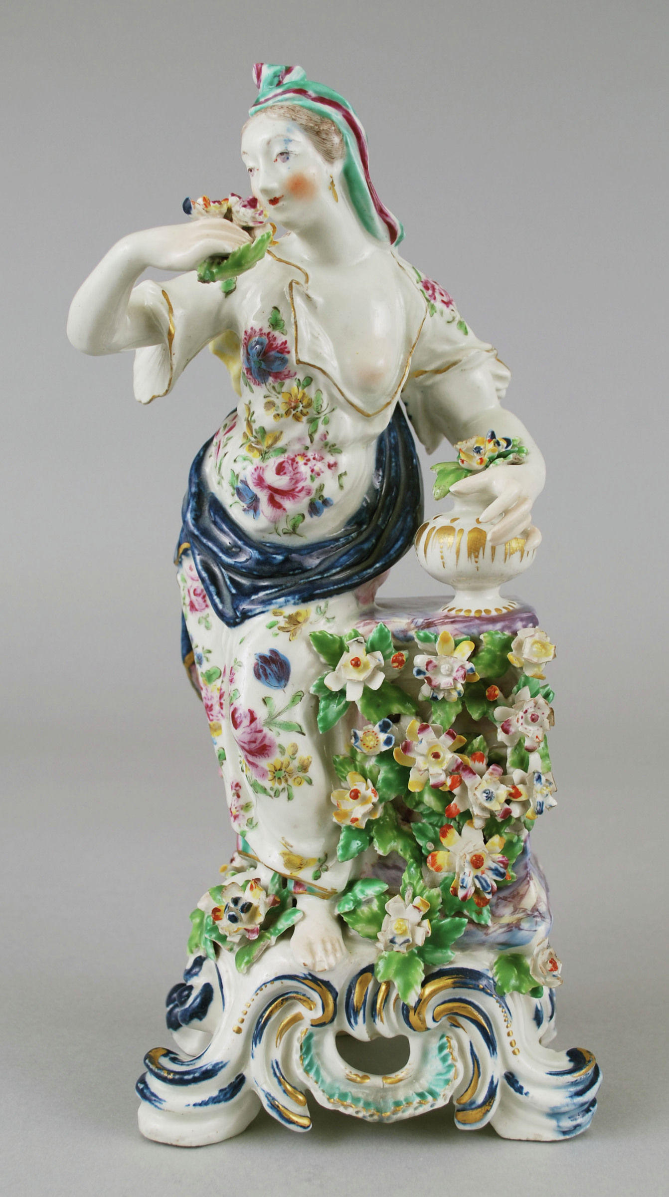 A Bow porcelain female figure standing on a painted scrolled base. She stands holding a bouquet of flowers in her right hand bent at the elbow towards her body. The other hand also holding flowers in resting on a short vase shaped vessel, possibly an incense burner that sits on a marbled pedestal covered with flowers and leaves from the front. Her dress is painted in various colored flowers with a blue and rose colored sash wrapped around her waist and back. The hair has green and burgundy colored ribbons painted.
