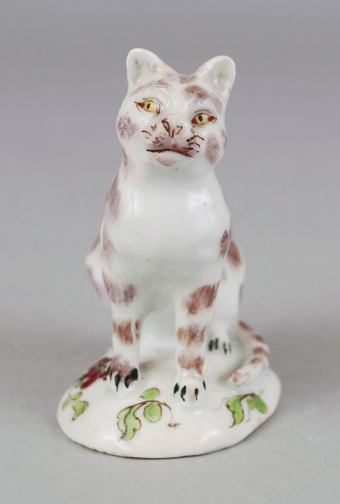 Small seated Bow porcelain cat of white color with brown patches. The eyes are painted yellow and paws have black lines for nails. The tail curves around next to the right of the feet. The cat sits on a circular base with painted flowers and green vines.