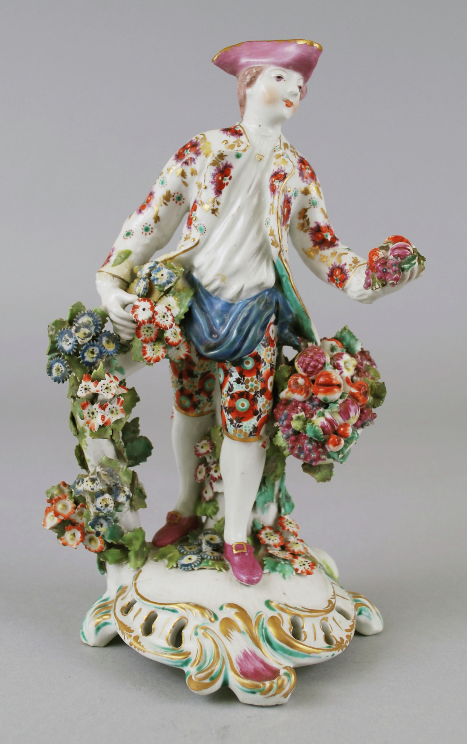 Soft-paste porcelain figure of a man selling fruit, emblematic of autumn, standing in full figure on a pierced rococo base highlighted in gold, green and puce, to his right a flowering branch that offers the figure support, around his waist a blue apron bag holding a bunch of various fruits and additional fruits are in his outstretched left hand, wearing flowered britches and jacket, with puce hat and shoes.