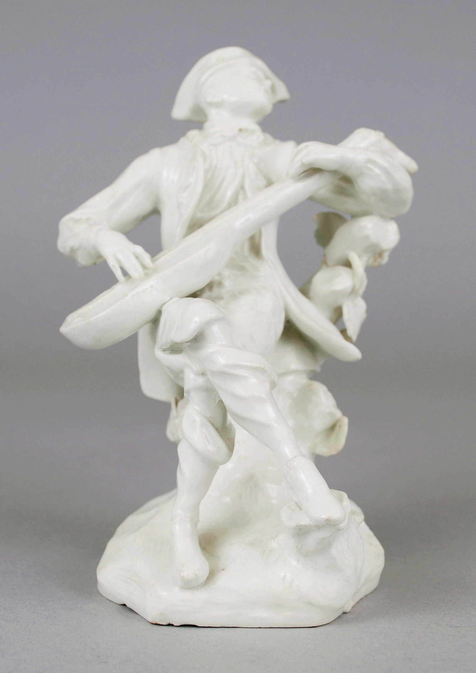 White porcelain figure of a seated man playing the mandolin, seated on a tree stump with flowery branch on molded, rocky base, his legs crossed and his head turned to one side as though singing, wearing 18th century garb and hat.