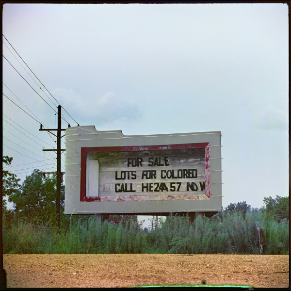 """A barren field fills the foreground; its far edge is lined with tall weeds. At the center of the image, against a partly cloudy sky, is a billboard that bears the text, """"For Sale  Lots for Colored  Call HE24457  Now"""".  Beside the sign are wire laden telephone poles."""
