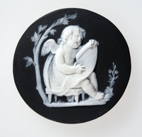 Round black jasper medallion with white relief of Cupid singing under a tree