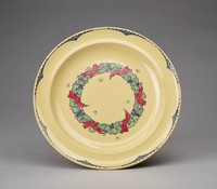 """Round dinner plate of caneware in the concave shape decorated in the """"Nerots"""" pattern, the border with a scalloped edge in blue underglaze enamel with a modified fish scale pattern likewise in blue at the indentations, the center with an oval wreath of stylized green flowers and blue berries with six bright red birds resting on it, with six small line-drawn butterflies scattered about."""
