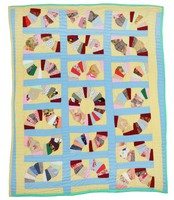 Grandmother's fans quilt on cream background with light blue borders, knit fabrics.