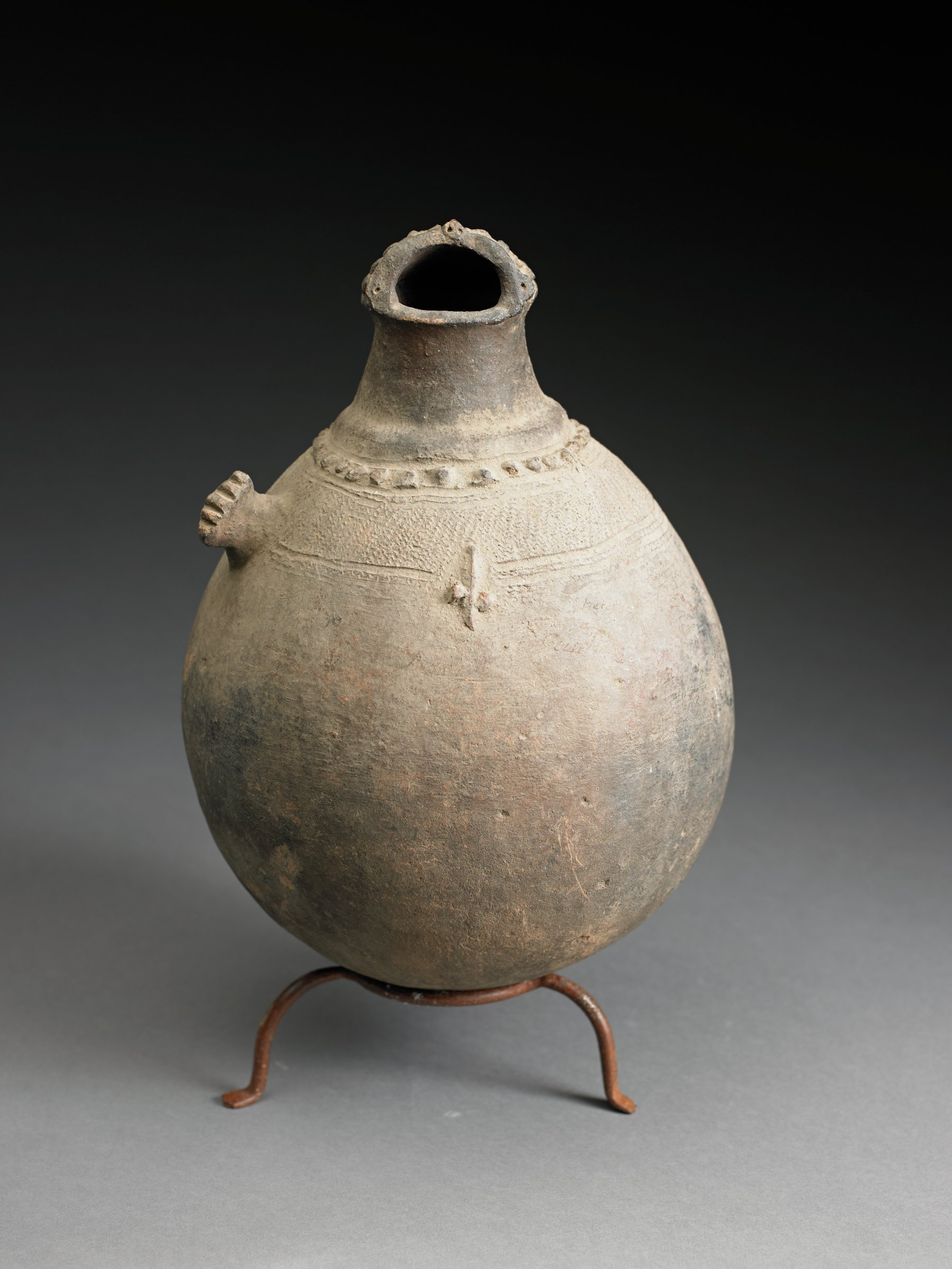 Ovoid, figurative vessel has round bottom, neck, and abstract head with wide mouth and bumps on back of head.  Body has single, short arm and raised bumps, possibly genitals.