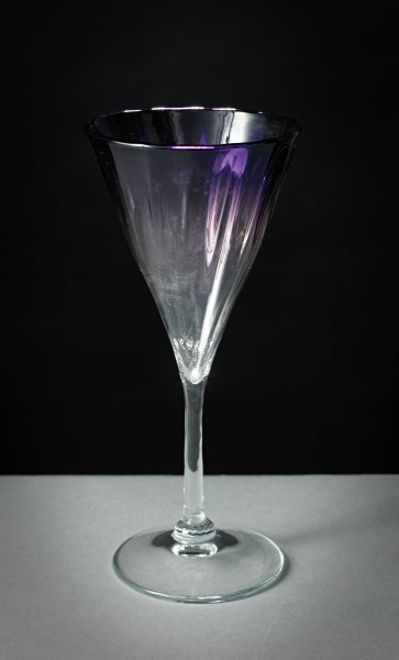 Tall, glass champagne flute with spirally-fluted, conical bowl, in a shade of deep purple that fades to clear at the bottom of the bowl, the clear glass stem is textured, the round foot also of clear glass.