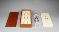 Wooden box with sliding cover, with felted title sheet and lining, and three wishbones cast in bronze, ceramic, and rubber.