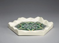 Hexagonal creamware ashtray with molded diamond pattern around the edge, the center with a molded and silkscreened pattern of wedges in a star design comprised of various geometric forms against a lattice ground, colored in shades of black, green, yellow, and white.