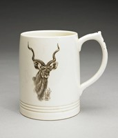 """Large cylindrical creamware mug with pointed loop handle, shape number 3810 by Keith Murray, covered with a matt moonstone glaze, with commemorative design for South African Game Series. An antelope head is printed in black ink on one side. On the other side of the mug is a multi-color printed map of South Africa with animals that are popular to each region represented, a green laurel border, and antelope head above the map. Beneath the map is a yellow banner that reads, """"SUID-AFRIKA; SOUTH AFRICA""""."""