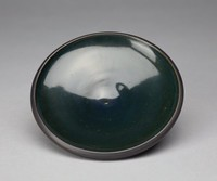 Slightly convex, open shape. The exterior is matte black with faint line impressions, creating a swirl effect with the base's bottom as the center of the swirl. The dish's interior is glazed and has a dark green cast. The glaze is smooth and even.