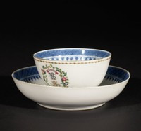 A tea bowl with matching saucer decorated with the crest, motto, and initials of ML of Loch, Drylaw. Also small flowers in overglaze enamel.