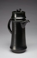 Tall, slender coffee pot of white stoneware covered with a black matt satin glaze (ravenstone), the long body cylindrical in shape with a slightly flared lower body which is then truncated in to form a narrower foot, with loop handle and short spout extending from right below the shoulder, the tall cover likewise cylindrical in shape with slightly flared lower edges, the knop in the form of an inverted strap handle.