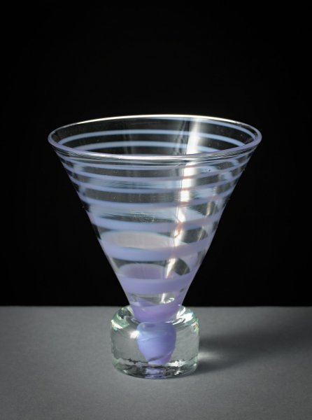 Stemless, conical drinking glass of clear glass and decorated with a thread of purple glass that spirals around the cone of the bowl and into the foot, which is comprised of a thick, clear cube-shaped blob of glass.