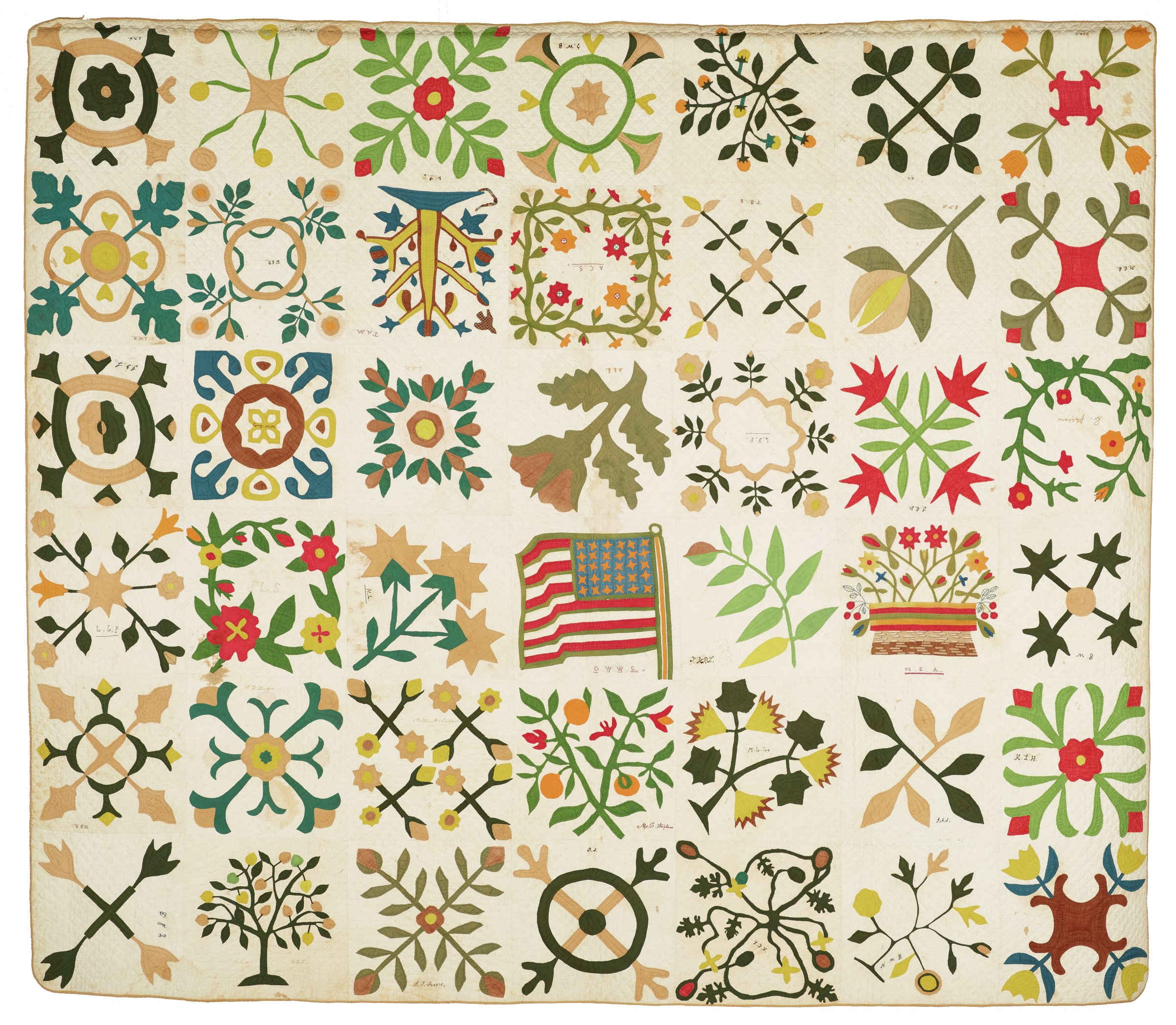 Large, colorful album quilt comprised of 42 blocks of applique on solid cotton, each made by a different quilter in a different design, the blocks include flowers and floral motifs based on Alabama native flora, in the center is the United States flag, appearing to flutter gently in a light breeze, bearing 30 stars, the backing a plain muslin.