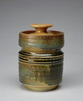 Covered jar of creamy, glazed stoneware of cylindrical shape with an indented band around the main body about one-third down from the top with which to grip the jar, the lower body truncated to form a narrower foot, the recessed, flat cover with mushroom finial, the entire jar covered with an irregular, mottled glaze in shades of green, brown and beige, the cover with a uniform tan glaze.