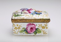 Small, rectangular enameled copper box decorated with colorful flowers in relief and with small gold leafy elements, with gilt metal mounts.