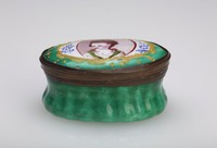 Small oval enameled copper box, the ground emerald green and the lid painted in a gold-framed reserve with the portrait of a woman with roses in her hair, on either side of her are simple blue floral elements.