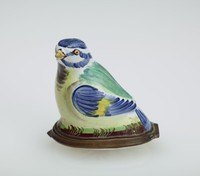 Small enameled copper bonbonnière in the shape of a bird with white body and blue and yellow wings and green on the back, with brown under the yellow beak, the underside painted with a floral spray, with gilt metal mounts.