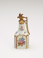 Small enameled copper scent bottle of tapering flask form with white ground and decorated with floral sprays and gilding, with a gilded lattice pattern at each truncated corner, with gilt metal mounts and stopper in the form of a bird attached with a chain to the mount.