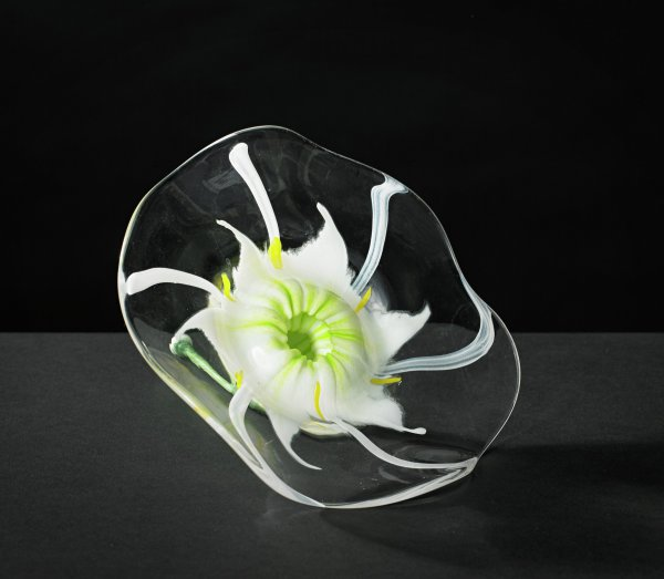 Large round, clear glass Cahaba Lily flower with a mottled, light-green stem and opaque white center with green and yellow accents in the form of six tentacles extending from the center and six smaller yellow blobs around the center of the flower.