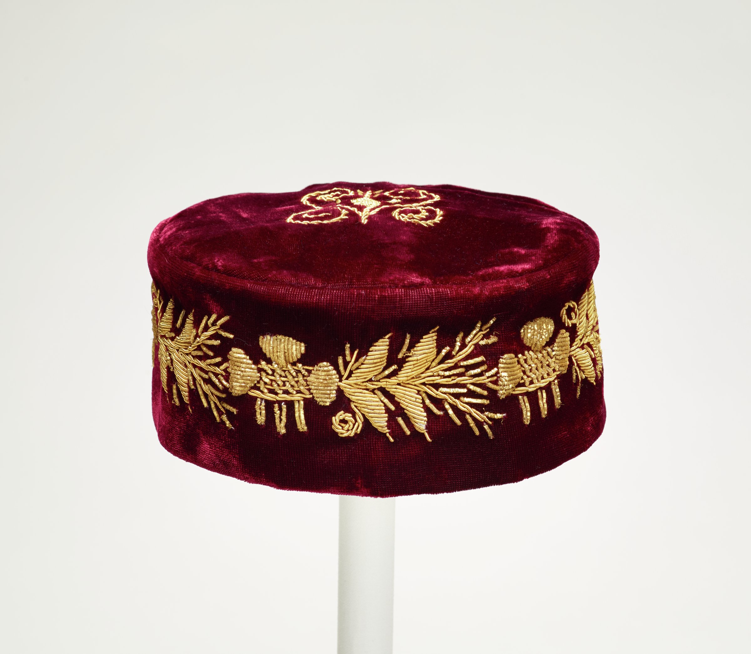 Red velvet man's kufi-style hat embellished with gold thread.