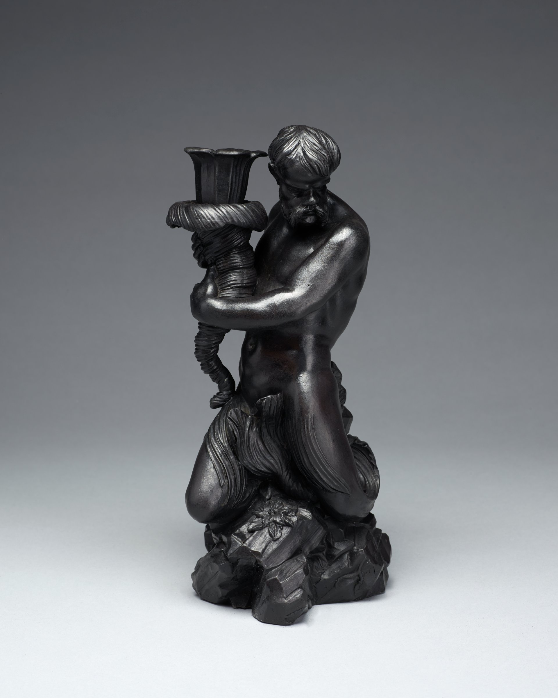 Candleholder of black basalt in the form of a bearded, naked Triton with seaweed clinging to his thighs sitting atop a rocky base and holding in both hands a whorled conch shell that functions as the candleholder.