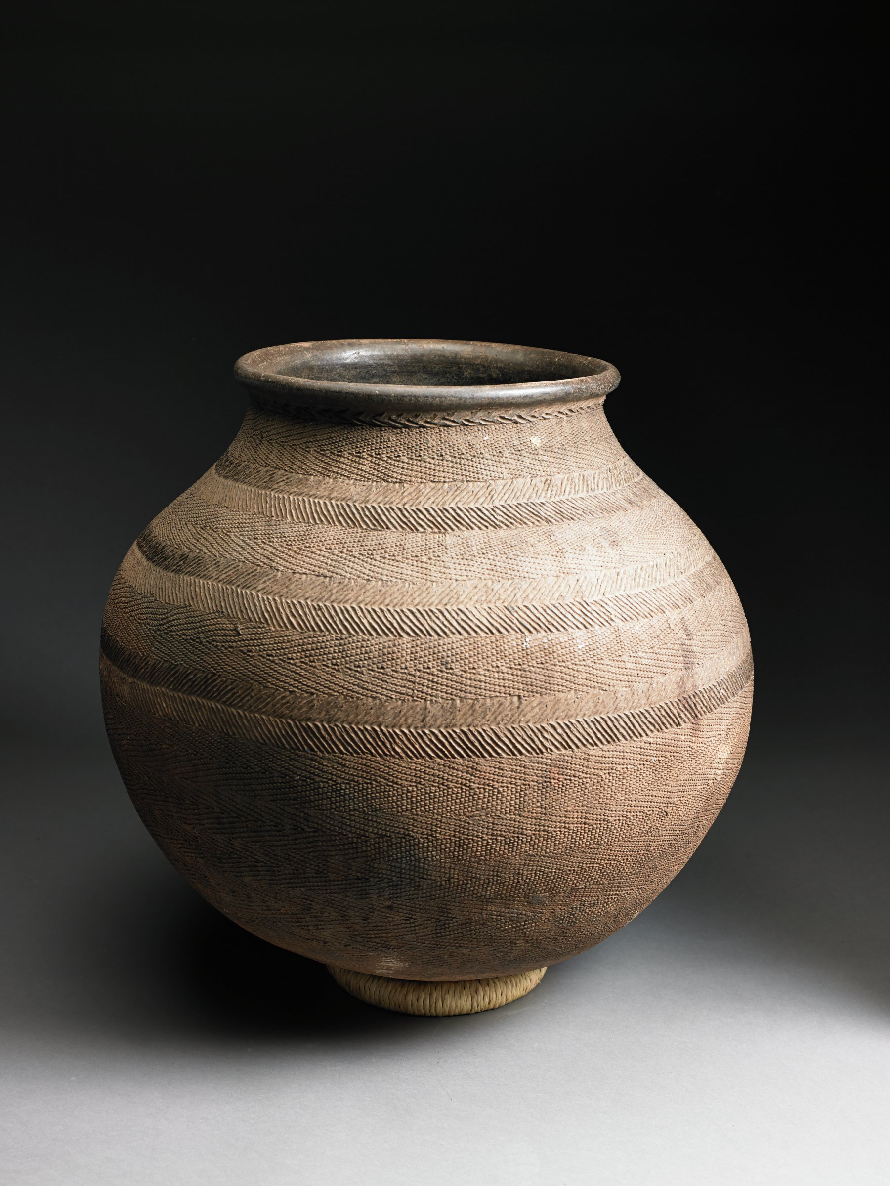 Dark brown, ovoid vessel narrows at neck; body covered with bands of incised diagonal lines and herringbone pattern.