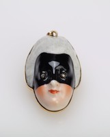Small locket in the form of a female head wearing a tall white wig and a black mask that covers the upper part of the face, with rosy cheeks and red lips, in gilt metal mount, the locket opens in back to reveal a hollow compartment.