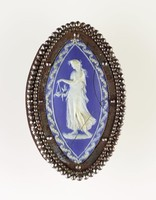 Elongated oval or leaf-shaped dark blue jasper medallion with white relief of female holding lamp and foliage, set in steel as buckle, several cracks