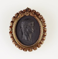 Oval black basalt medallion with relief profile portrait of Claudius, set in chased gold metal mount with rolled ribbon edge, with ring for hanging as pendant