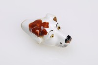 Small porcelain whistle in the form of a dog's head, the dog white with brown spots, yellow eyes, and black nose.