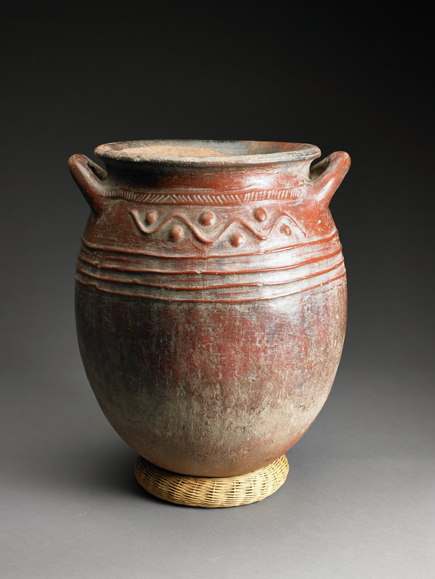 Reddish, ovoid vessel with wide mouth and handles just below rim has parallel raised ridges on shoulder.