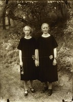 Two young women hold hands standing by the side of a dirt road or path. Behind them are bushes and trees. The women wear simple, short-sleeved, knee-long black dresses and look directly at the camera.