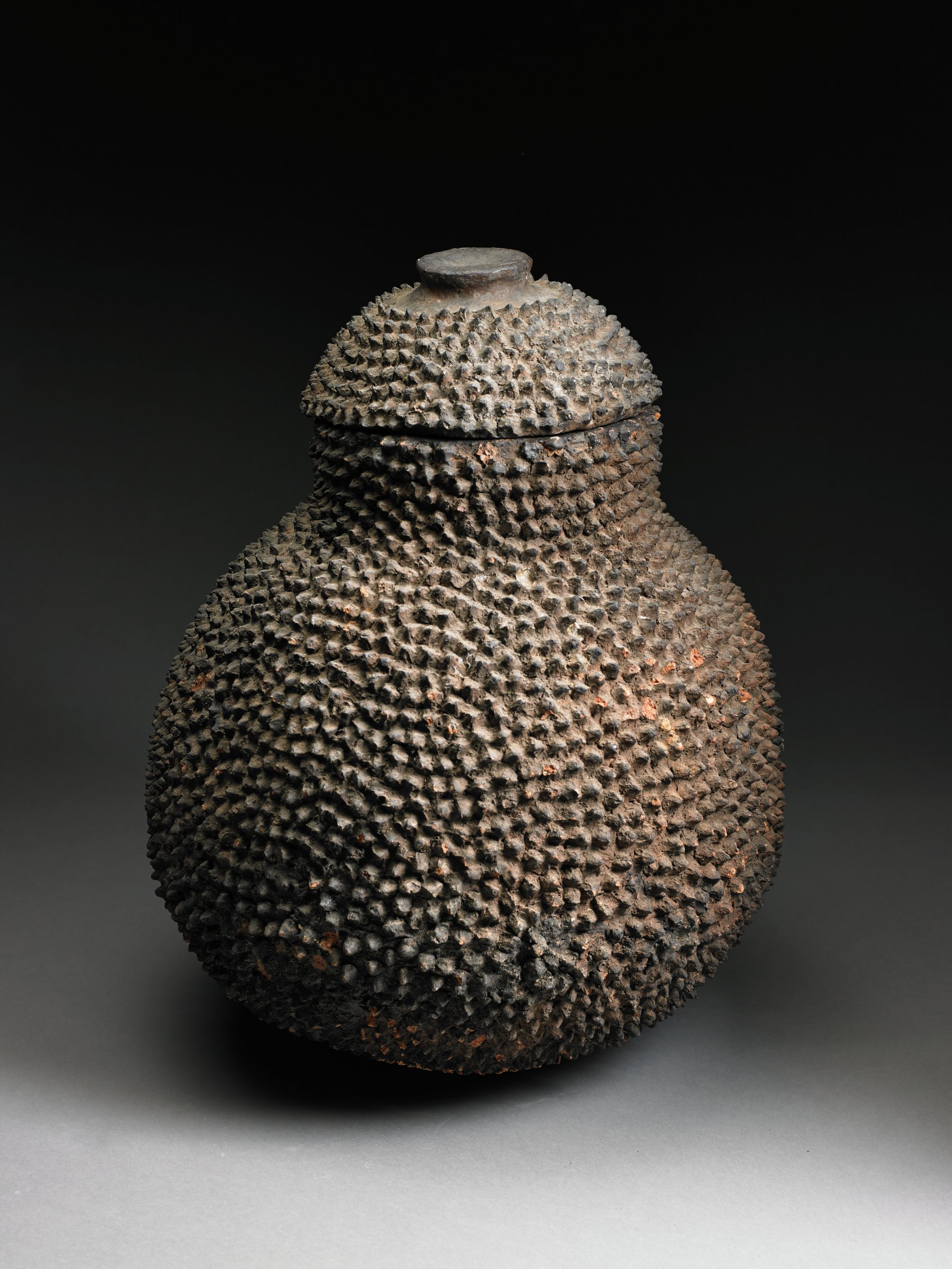 Pear-shaped vessel has short, narrow foot and lid with knob handle; body and lid covered with pinched points.