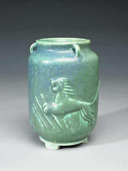 Vase of reddish-brown stoneware, the chunky body resting on three square feet, the neck short, the lip slightly flared, with three rings extending from lip to shoulder, the body with molded decoration in relief with on one side the image of a man, or warrior, on his knees, his knife drawn and raised in his right hand, his left arm outstretched, on the other a pouncing lion in a landscape, perhaps referring to the story of Hercules and the Nemean lion, the vase is covered with a thick, opaque, turquoise glaze with darker blue streaks over a white glaze, the foot mostly white.