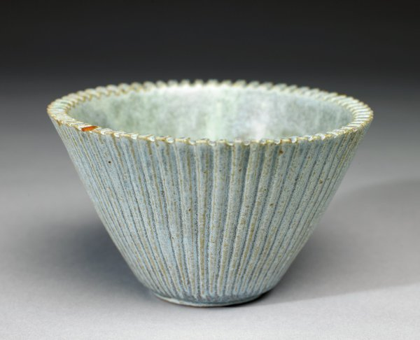 Small bowl of beige stoneware, funnel-shaped and with ribbing, or fluting, on the exterior, covered with a light gray-blue glaze that allows the color of the clay to show through on the edges of the ribbed decoration, the interior glaze ranging from light blue to beige to brown in an irregular and mottled fashion.