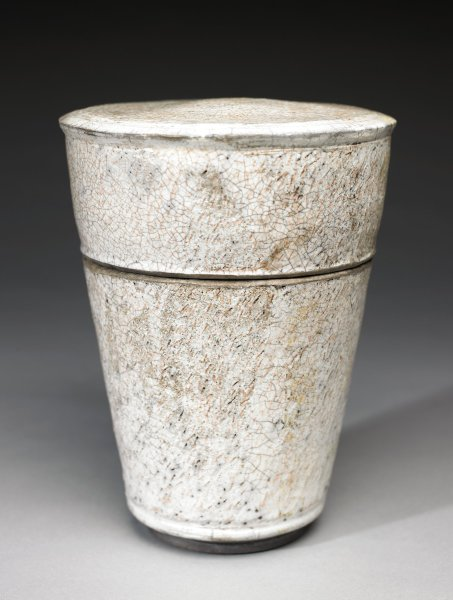 Tall, heavy, covered jar of blackish raku glazed and fired stoneware, the body conical and the cover large and flat, the glaze a creamy opaque white with crackling and numerous glaze imperfections that give the piece a rustic feel, the foot left glaze free.