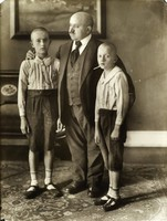 The father is standing between two young boys. The boys are dressed alike in white, striped, buttoned shirts with dark, short pants, closed sandals and white socks. Both have shaved heads and look at the camera. The father look off to the left, is dressed in suit and tie and puts his arms around both boys. The floor is covered by an oriental carpet. At the wall behind is a piece of furniture above which hangs a painting on the wall.