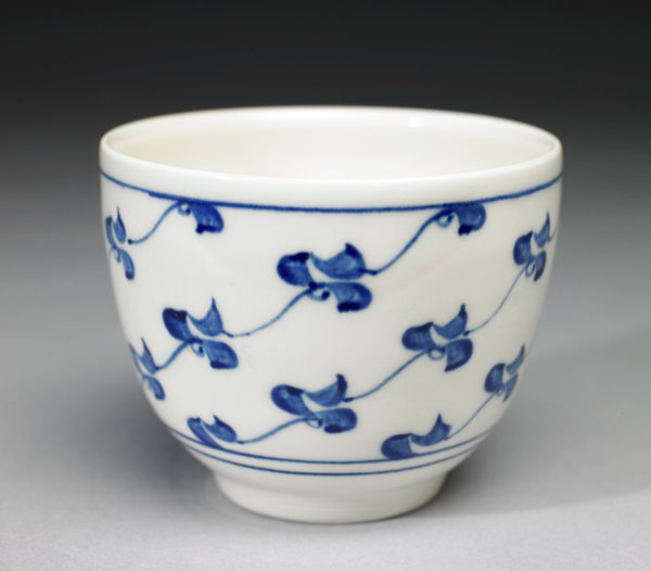 Small bowl of white stoneware with narrow foot and decorated in underglaze blue with bands encircling the body below the lip and at the lower edge, the main body decorated with an abstract repeating wavy, or scrolled, pattern on the diagonal, each element connected by thin, slightly wavy blue lines.