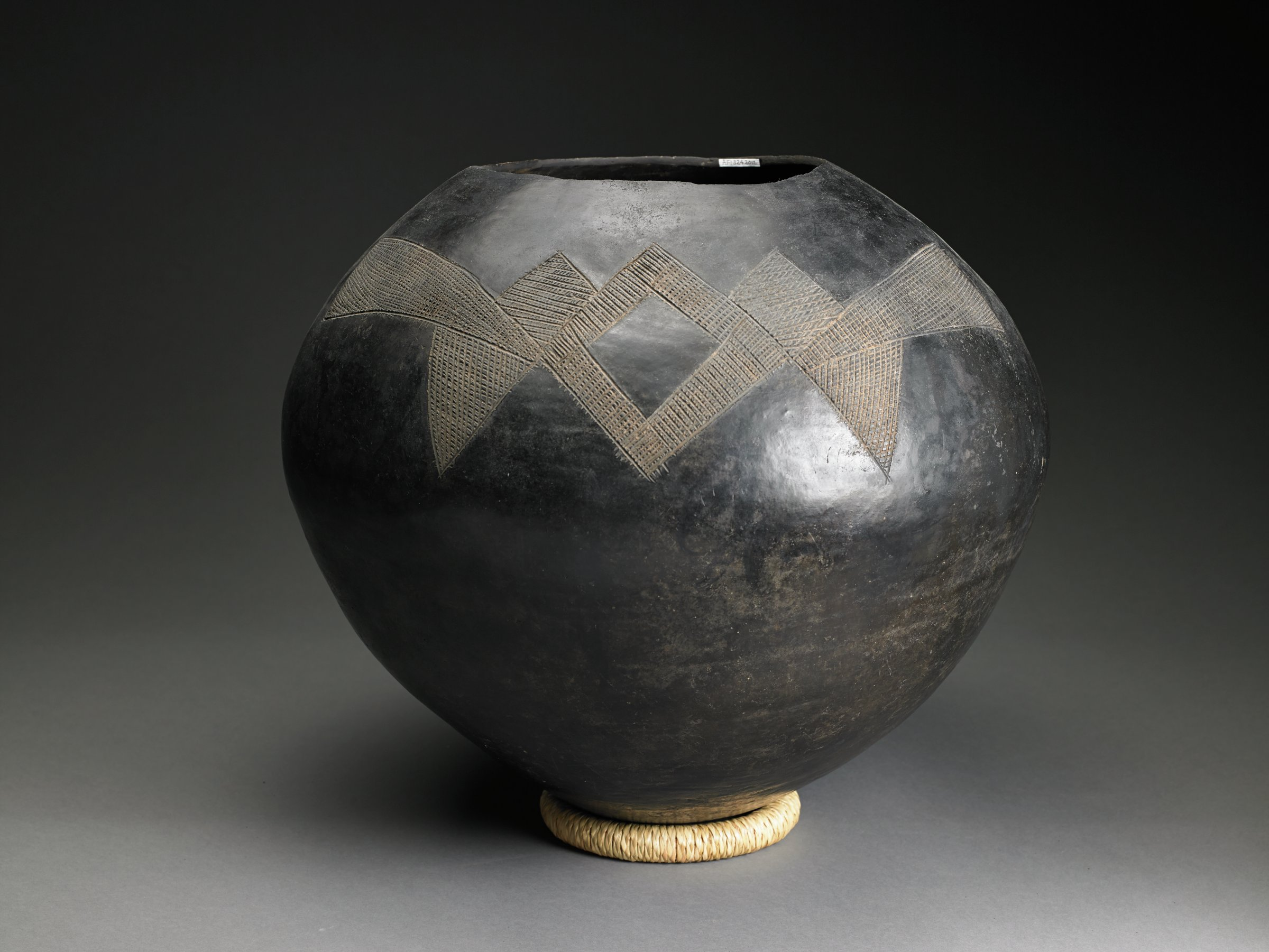 Round, black vessel has round mouth with no rim.  Horizontal geometric designs incised into shoulder.
