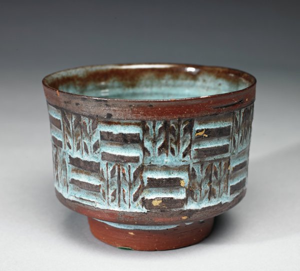 Deep, round, footed bowl of red earthenware, the sides are decorated with an alternating pattern of horizontal lines and stylized sheaves of wheat, the bright blue glaze of the body (the foot is left unglazed) pools in the crevices of the design to leave the color of the clay visible on the raised portions, the glaze also thins at the rim to reveal the color of the clay beneath.