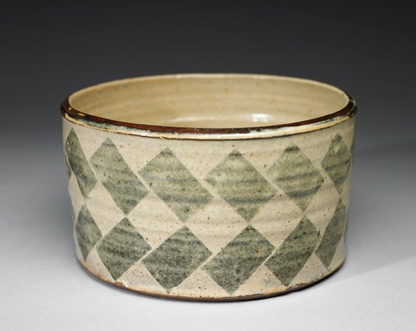 Large, heavy, round bowl of reddish brown stoneware, with flat bottom and covered with a creamy, opaque glaze, the rim brown, the body of the bowl with a pattern of two rows of greenish-gray rectangles, each tilted and meeting at opposite corners to form diamond patterns in between.