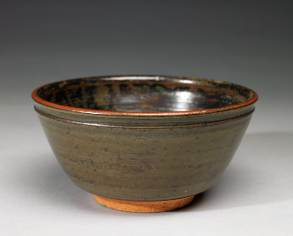 Deep, round, footed bowl of coarse orangey beige-colored stoneware covered with a gray-brown-green-reddish mottled glaze, the foot rim left without glaze to reveal the color of the clay beneath.