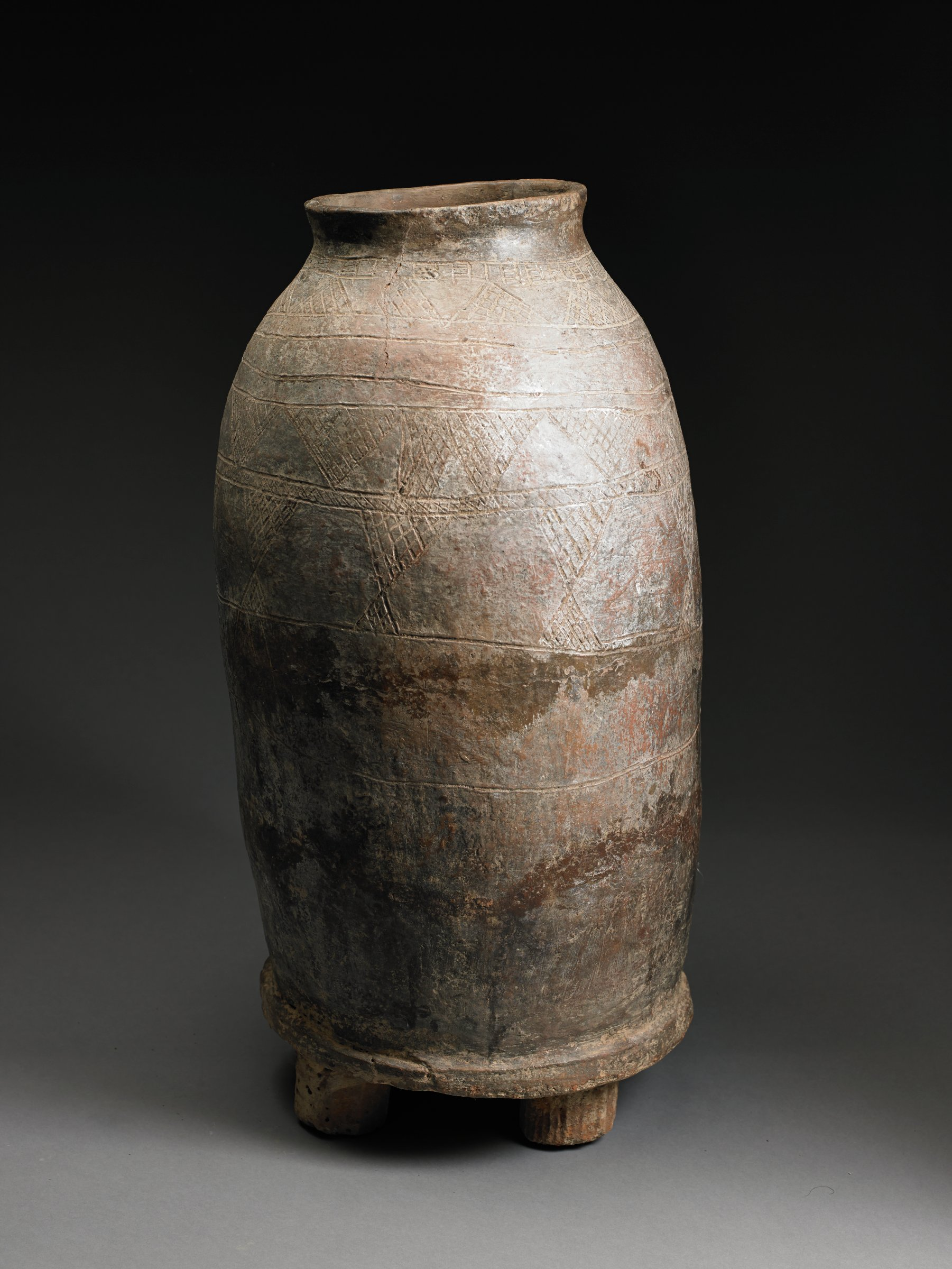 Brownish-gray vertical vessel has short neck with narrow mouth. Flat bottom rests on short legs. Body of vessel adorned with incised triangles filled with diamond patterns.