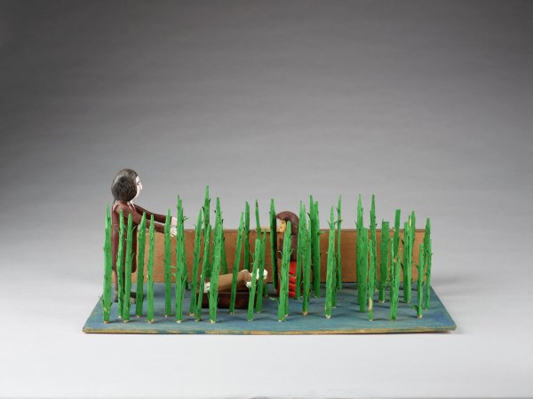 Two adult figures and baby Moses in basket behind tall thin bullrushes.