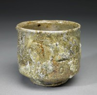 Small, deep, irregularly round, footed tea bowl of buff-colored stoneware covered with a thick, irregular, splotchy, blistered and drippy glaze in natural shades of beige, white, and gray, the interior covered with a glassy green, crystal-like glaze.