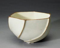 Small, footed bowl of yellowish-beige earthenware comprised of six sections each connected in an irregular way such that the bowl appears to rotate or turn, covered with a white glaze that is uneven and puckered in spots, the raised seams where each of the six sections meet as well as the rim of the bowl are left without glaze and reveal the raw clay beneath.