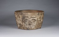Large, flat bottomed bowl with slightly out slanting walls with the face of the Sun God appliqued on the front; oval eyes with heavy brows; large hooked nose; face framed by rows of buttons and scrolls; narrow high flanges